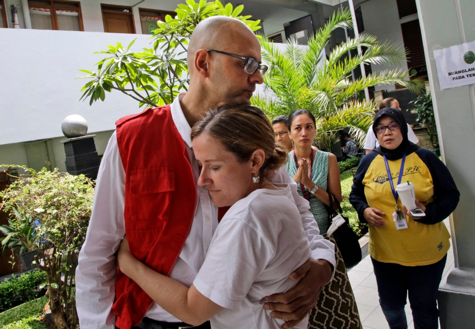 Canadian teacher Neil Bantleman, left, is hugged by his wife Tracy prior to the start of his trial hearing to listen to the prosecutor's demand at South Jakarta District Court in Jakarta, Indonesia, Thursday, March 12, 2015.  (AP Photo/Dita Alangkara)