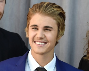 FILE - In this March 14, 2015 file photo, honoree Justin Bieber arrives at the Comedy Central Roast of Justin Bieber at Sony Pictures Studios in Culver City, Calif. Bieber's former neighbors Jeffrey and Suzanne Schwartz sued the pop singer in Los Angeles on Thursday March 19, 2015, claiming he spit on Jeffrey Schwartz during a dispute in March 2013 and caused emotional distress with loud parties and unsafe driving in their neighborhood. (Photo by Jordan Strauss/Invision/AP, File)