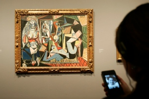 A visitor looks at 'Women of Algiers O (after Delacroix), 1955' by Pablo Picasso with an electronic guide at the exhibition, 'Picasso, Challenging the Past' at the National Gallery in London, Tuesday, Feb. 24, 2009. (AP Photo/Sang Tan)
