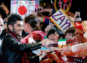 "In this Sunday, Nov. 3, 2013 file photo, Zayn Malik of One Direction gives his autograph to Japanese fans during an event for their film ""One Direction: This Is Us"", in Makuhari near Tokyo. (AP Photo/Koji Sasahara)"