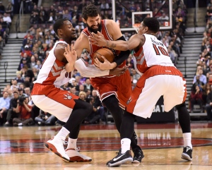 Chicago Bulls' Nikola Mirotic (44) battles for a loose ball against Toronto Raptors' Terrence Ross and DeMar DeRozan (10) during first half NBA basketball action in Toronto on Wednesday, March 25, 2015. (The Canadian Press/Frank Gunn)