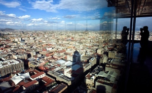 A man peers out over Mexico City on a clear afternoon Tuesday, Jan. 30, 2007. (AP Photo/Gregory Bull)