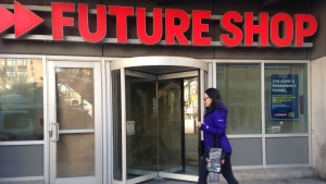 A woman walks past a Future Shop store with its doors shuttered in Toronto Saturday March 28, 2015. (Kevin Hoppler /CP24)