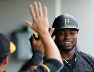 Pittsburgh Pirates' Gregory Polanco, center, high-fives his teammates in the dugout after hitting a solo home run in the first inning of an exhibition spring training baseball game against the Minnesota Twins, Friday, March 27, 2015, in Fort Myers, Fla. (AP Photo/Brynn Anderson)