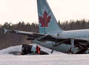 An investigator stands near Air Canada flight AC624 that crashed early Sunday morning during a snowstorm, at Stanfield International Airport in Halifax on Sunday, March 29, 2015. Air Canada says 25 people were taken to hospital. The flight had 133 passengers and five crew members. (Andrew Vaughan /The Canadian Press)