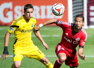 In this file photo, Toronto FC defender Justin Morrow, right, eyes the ball next to Columbus Crew midfielder Ethan Finlay, left, during first half MLS soccer action in Toronto on Saturday May 31, 2014. (Nathan Denette /The Canadian Press)