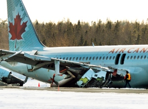An investigator inspects Air Canada flight AC624 that crashed early Sunday morning during a snowstorm, at Stanfield International Airport in Halifax on Sunday, March 29, 2015. Air Canada says 25 people were taken to hospital. The flight had 133 passengers and five crew members. THE CANADIAN PRESS/Andrew Vaughan