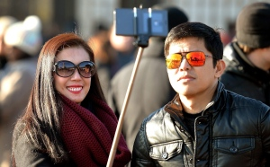 In this Jan. 23, 2015, file photo, tourists use a 'selfie stick' in London. (AP Photo/PA, John Stillwell)