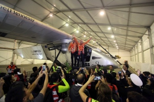 Pilots Andre Boschberg, center left, and Bertrand Piccard, at right, pose for photos with their solar powered plane in a hangar at Chongqing Jiangbei International Airport in southwest China's Chongqing Municipality, Tuesday, March 31, 2015. (AP Photo)