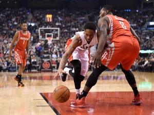 Toronto Raptors' DeMar DeRozan and Houston Rockets' Joey Dorsey battle for a loose ball during first half NBA action in Toronto on Monday, March 30, 2015. (The Canadian Press/Frank Gunn)