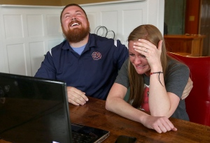 In this Monday, April 6, 2015 photo, Joel Burger and Ashley King react at King's home in New Berlin, Ill., after learning from a New York public relations firm that Burger King has offered to pay the expenses and provide gifts for their wedding because of their interesting connection to the fast food restaurant chain. (AP Photo/The State Journal-Register, David Spencer)