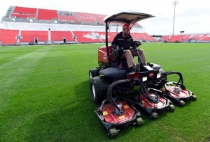 A lawnmower cuts grass in front of new upper stands being constructed for the BMO Field expansion in Toronto on Friday, April 10, 2015. (Frank Gunn /The Canadian Press)