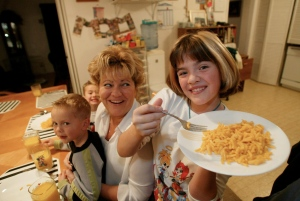 Ten year-old Samantha Dame serves up some Kraft Dinner to her mother Connie and siblings Austin, 4, (on lap), and Brock, 6, (behind), for supper Monday Nov. 10, 2003, in Winnipeg. (CP PHOTO/ Ruth Bonneville)
