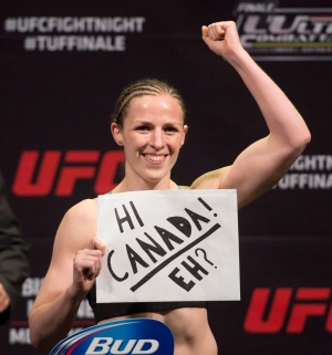 """Canadian bantamweight Sahah Kaufman, of Victoria B.C., raises her fist and a Canada sign at the weigh in for the UFC's """"The Ultimate Figher Nations"""" event in Quebec City on Tuesday, April 15, 2014. Canadian bantamweights Alexis Davis and Kaufman are set to fight for the third time. THE CANADIAN PRESS/Jacques Boissinot"""
