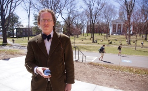 """Jonathon Keats poses holding a version of his """"millennium camera"""" designed to make a 100-year-long exposure on the Amherst College campus Thursday, April 16, 2015, in Amherst, Mass. Keats, a San Francisco-based writer who describes himself as an experimental philosopher and conceptual artist, has designed a camera he plans to perch atop a church-less steeple on the Amherst College campus, hoping the device will chronicle climate change by making a 1,000-year-long photograph of the Holyoke Range in western Massachusetts. (AP Photo/Stephan Savoia)"""