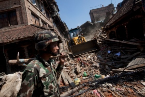A member of the Nepalese army walks through a damaged area caused by Saturday's earthquake, in Bhaktapur on the outskirts of Kathmandu, Nepal, Monday, April 27, 2015. A strong magnitude earthquake shook Nepal's capital and the densely populated Kathmandu valley on Saturday devastating the region and leaving tens of thousands shell-shocked and sleeping in streets. (AP Photo/Niranjan Shrestha)