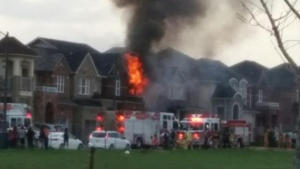 Fire crews battle a house fire in the Dufferin Street and Major MacKenzie Drive area in Vaughan Sunday May 3, 2015. (@amiccidinessuno /Twitter)