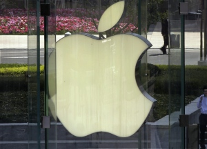 FILE - In this April 2, 2013, file photo, a man smokes near the logo of Apple in Shanghai, China.  AP Photo/Eugene Hoshiko,File)