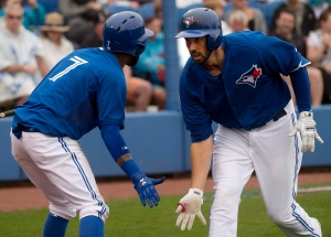Toronto Blue Jays infielder Chris Colabello, right, celebrates his his two run home run with Blue Jays shortstop Jose Reyes (7) during second inning Grapefruit League baseball action in Dunedin, Fla., on Friday, March 6, 2015. (The Canadian Press/Nathan Denette)