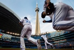 The CN Tower looms overhead as Toronto Blue Jays, from left to right, Danny Valencia, Chris Colabello, and Devon Travis take to the field before MLB baseball action against the Boston Red Sox in Toronto on Friday, May 8, 2015. (The Canadian Press/Darren Calabrese)