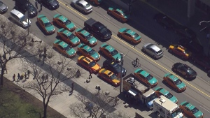 Taxis block lanes of traffic on Bay Street while protesting Uber at city hall on May 14.