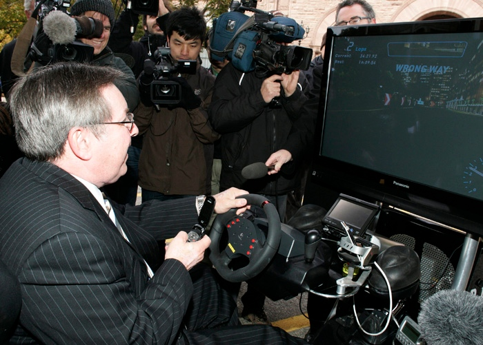 Ontario Transportation Minister Jim Bradley drives in a simulation car ride called D.U.M.B. (Distractions Undermining Motorists Behaviour) while trying to make a phone call at an announcement in Toronto, Tuesday, Oct.28, 2008. (THE CANADIAN PRESS/Jim Ross)