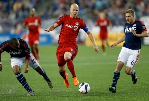 Toronto FC's Michael Bradley (4) sets up his scoring kick between New England Revolution's Teal Bunbury (10) and Scott Caldwell (6) during the second half of an MLS soccer game in Foxborough, Mass., Saturday, May 16, 2015. (AP Photo/Michael Dwyer)