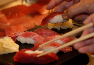 FILE - In this Sunday, Jan. 5, 2014 file photo, customers try sushi of a bluefin tuna (AP Photo/Shizuo Kambayashi, File)