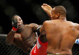 Anthony Johnson kicks Daniel Cormier during their light heavyweight title mixed martial arts bout at UFC 187 on Saturday, May 23, 2015, in Las Vegas. (AP Photo/John Locher)
