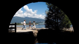 Pedestrians are framed underneath a vehicle bridge while walking along the Stanley Park seawall in Vancouver, B.C., on Sunday, Aug. 25, 2013. (The Canadian Press/Darryl Dyck)