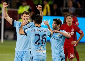 Manchester City midfielder George Evans, left, celebrates his goal with teammate Martin Demichelis (26) while playing against the Toronto FC during second half international club friendly soccer action in Toronto on Wednesday, May 27, 2015. (The Canadian Press/Nathan Denette)