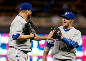 Toronto Blue Jays pitcher Mark Buehrle, left, and third baseman Josh Donaldson celebrate the Blue Jays' 6-4 win over the Minnesota Twins in a baseball game, Friday, May 29, 2015, in Minneapolis. Buehrle pitched a complete game and Donaldson had a three-run home in the fifth. (AP /Jim Mone)