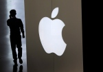 FILE - In this Sept. 5, 2014 file photo, a man walks into an Apple store in Beijing. (AP Photo/Andy Wong)