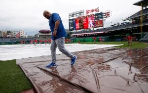 Toronto Blue Jays bench coach DeMarlo Hale walks over a water soaked tarp before an interleague baseball game against the Washington Nationals at Nationals Park on Monday, June 1, 2015, in Washington. (AP Photo/Alex Brandon)