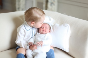 This image made available by Kensington Palace Saturday, June 6, 2015, taken by Kate, Duchess of Cambridge, at Amner Hall, eastern England in mid-May 2015 shows Britain's Princess Charlotte, right, being held by her brother, 2-year-old, Prince George. Britain's royals have been photographed by some of the world's leading photographers. But Prince William and Kate are continuing a more informal tradition begun two years ago with the first official portrait of Prince George, taken by his grandfather Michael Middleton. Charlotte was born May 2 and is fourth in line to the throne. (Duchess of Cambridge via AP)