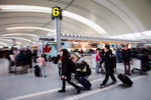 People carry luggage at Pearson International Airport in Toronto on December 20, 2013. (The Canadian Press/Mark Blinch)
