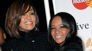 "In this file photo, singer Whitney Houston, left, and daughter Bobbi Kristina Brown arrive at an event in Beverly Hills, Calif. Brown is moving to hospice care after months of receiving medical care. Pat Houston says in a statement Wednesday, June 24, 2015, that Whitney Houston's daughter's ""condition has continued to deteriorate. Brown was found face-down and unresponsive in a bathtub of her Georgia home earlier this year. She underwent surgery to replace her breathing tube with a tracheostomy tube in February.  (AP Photo/Dan Steinberg, File)"