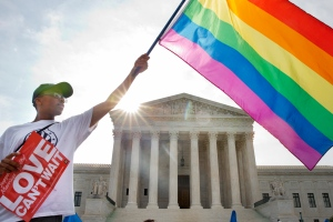 Carlos McKnight of Washington, waves a flag in support of gay marriage outside of the Supreme Court in Washington, Friday June 26, 2015.. (AP /Jacquelyn Martin)