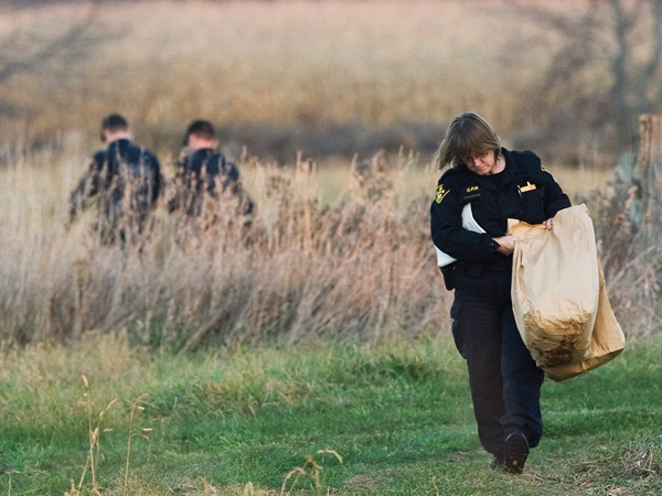 OPP officers walk out off deep brush with a bag of materials as police believe the body of 15-year-old Brandon Crisp may have been found by hunters just north of Barrie, Ont., on Wednesday, Nov. 5, 2008. (Nathan Denette / THE CANADIAN PRESS)