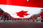 A massive Canadian flag is carried along the Canada Day Parade route through Port Credit in Mississauga, Ont., on Wednesday, July 1, 2015. (The Canadian Press/Peter Power)