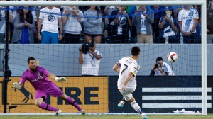 Los Angeles Galaxy forward Robbie Keane (7) scores on a penalty kick past Toronto FC goalkeeper Chris Konopka (1) during the first half of an MLS soccer game in Carson, Calif., Saturday, July 4, 2015. Keane scored three goals in their 4-0 win. (AP Photo/Alex Gallardo)
