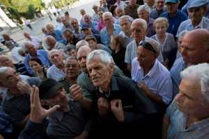 "Elderly people argue with a bank worker as they wait to be allowed into a bank to withdraw a maximum of 120 euros ($134) for the week in Athens, Monday, July 6, 2015. Greece's Finance Minister Yanis Varoufakis has resigned following Sunday's referendum in which the majority of voters said ""no"" to more austerity measures in exchange for another financial bailout. (AP Photo/Emilio Morenatti)"