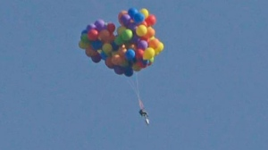 A lawn chair, strapped to dozens of helium balloons, is seen in this photo taken by Tom Warne and posted on Twitter.