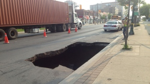 A large sinkhole is pictured on Eglinton Avenue near Richardson Avenue Tuesday July 7, 2015. (Michael Nguyen /CP24)