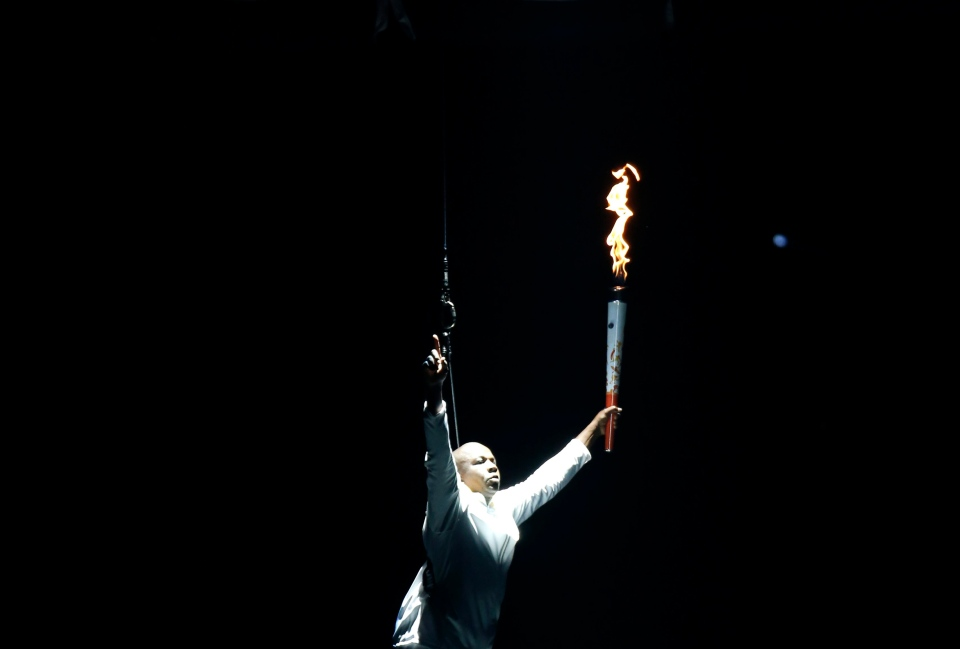 Retired Canadian sprinter Donovan Bailey is lowered to the stage with the Pan Am torch during the opening ceremony of the 2015 Pan Am Games in Toronto Friday, July 10, 2015. (AP Photo/Julio Cortez)
