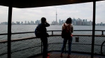People photograph the City of Toronto skyline from the ferry as they make their way to the Toronto Islands in Toronto. (THE CANADIAN PRESS/Nathan Denette)