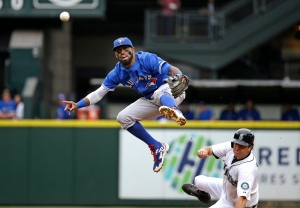 Toronto Blue Jays shortstop Jose Reyes, left, leaps out of the way after forcing out Seattle Mariners' Seth Smith at second base and throwing to first in the third inning of a baseball game Saturday, July 25, 2015, in Seattle.  (AP /Elaine Thompson)