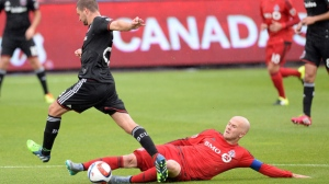 Toronto FC midfielder Michael Bradley (4) slide tackles D.C. United's Perry Kitchen during second half MLS soccer action in Toronto on Saturday June 27, 2015. THE CANADIAN PRESS/Frank Gunn
