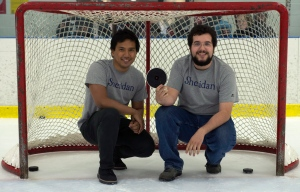 Sheridan College student designers Kristoffer Pascual, right, and Ryan Veiera pose for a portrait with their specially designed hockey puck for the blind on July 30, 2015 in Oakville, Ont. THE CANADIAN PRESS/Jon Blacker