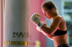 """FILE - This July 15, 2015, file photo shows mixed martial arts fighter Ronda Rousey working out at Glendale Fighting Club in Glendale, Calif. Paramount Pictures said Monday, Aug. 3, that it has acquired the rights to Rousey's autobiography """"My Fight/Your Fight,"""" with plans for Rousey to play herself in the adaptation. (AP Photo/Jae C. Hong, File)"""